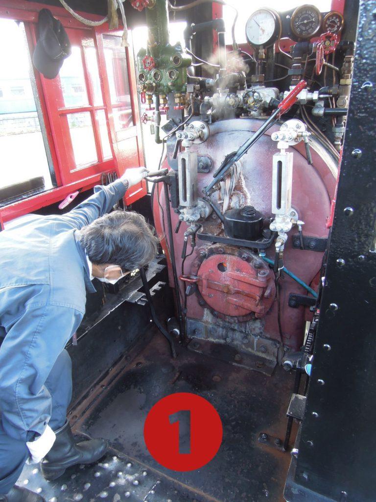 焚き口の覗き窓から炎を見ながら燃料を調節しているところ